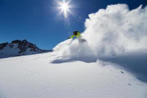 alpine skiër op de piste, skiën bergafwaarts foto