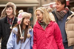 tiener gezin wandelen langs besneeuwde stad straat in skiresort foto
