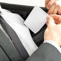 het plaatsen van een blanco visitekaartje in de binnenzak van een jas foto