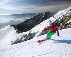 skiër skiën bergaf in het hooggebergte tegen zonsondergang foto