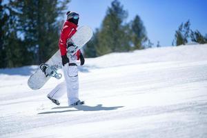 snowboarder die snowboard houdt foto