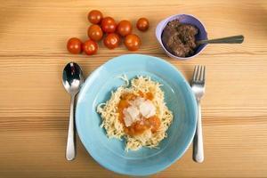 couvert voor een kind met pasta en tomaten foto