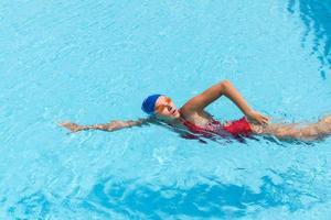 vrouw zwemt freestyle in het zwembad foto