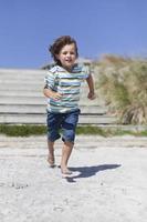 jongen draait op zandstrand foto