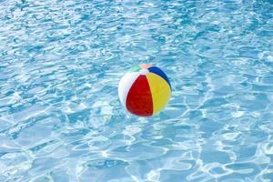 strandbal drijvend op het oppervlak van het zwembad foto