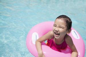 schattig klein meisje zwemmen in het zwembad met een roze buis foto