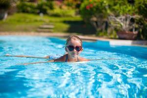 klein schattig gelukkig meisje zwemmen in het zwembad