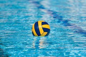 een gele en blauwe bal drijvend in een zwembad foto