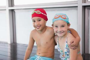 schattige kleine kinderen zitten bij het zwembad foto