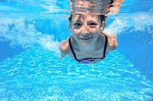 gelukkig actieve onderwater kind zwemt in het zwembad