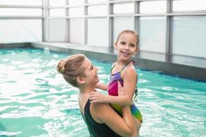 schattig klein meisje leren zwemmen met mama foto