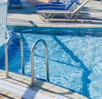 zwembad met ligstoelen foto