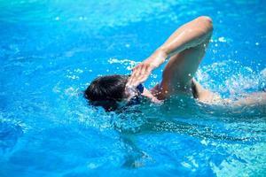 jonge man zwemmen in een zwembad foto