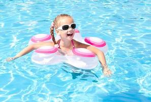 glimlachend meisje in zwembad foto