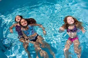 jonge meisjes zwemmen achteruit in het zwembad foto