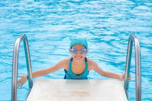 klein meisje in het zwembad. zomer buiten foto
