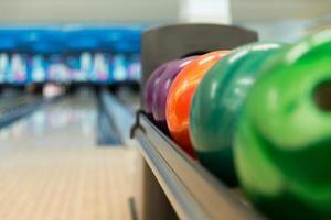rek van kleurrijke ballen op een bowlingbaan foto