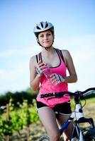 gezonde vrolijke jonge vrouw rijden mountainbike buiten op het platteland foto