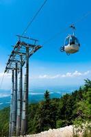 mountainbike op kabelbaan lift over alpine bos.
