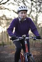 vrouw rijden mountainbike door bossen foto