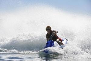 jonge man jetski rijden in snelheid op meer foto