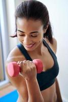 lachende vrouw training met halters foto
