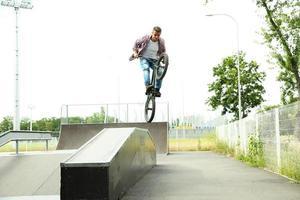 jongen springen met zijn bmx fiets op skatepark foto