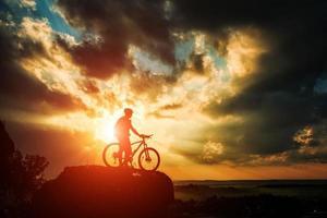 silhouet van een fietser en fiets op hemelachtergrond. foto