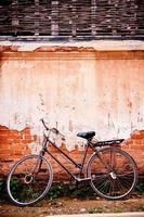 oude fiets geparkeerd naast het vintage oude huis. foto