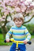 kleine peuter jongen jongen rijden met zijn eerste fiets foto