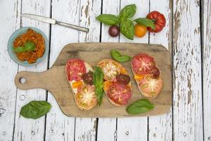sneetjes brood met erfstuk tomaat op snijplank foto