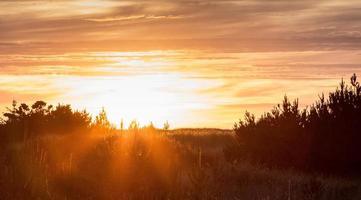 oranje stralen en zonsondergang over een strandhoofd foto