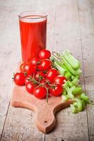 tomatensap in glas, verse tomaten en groene selderij foto