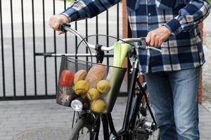 man en fietsmand vol boodschappen