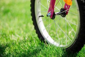 de fiets van kinderen op groen gras, sluit omhoog foto