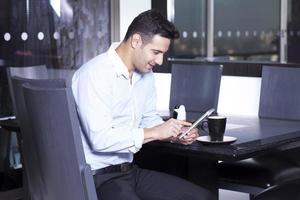 zakenman gebruikt zijn digitale tablet in de eetkamer foto