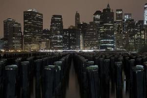 lagere skyline van manhattan nacht uitzicht vanaf brooklyn bridge park foto