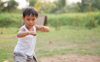 gelukkige jonge jongen van Azië die kungfu speelt die pret heeft foto