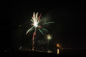 prachtig vuurwerk dat nieuwjaar op het strand viert foto