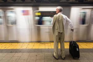 senior zakenman wachten op de trein op metrostation foto