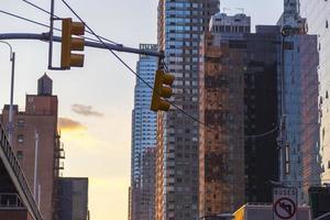 verkeerslicht met wolkenkrabbers op achtergrond in nyc bij zonsondergang foto