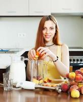 positieve vrouw koken van perziken foto