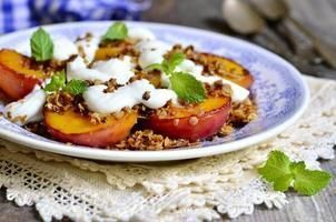 gegrilde perziken met granola en slagroom. foto