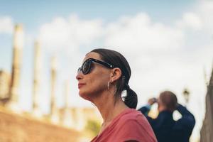vrouwelijke toerist die met zonnebril architectuur van Rome bewondert. foto