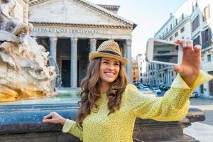 jonge vrouw selfie maken in de buurt van pantheon in rome, Italië foto