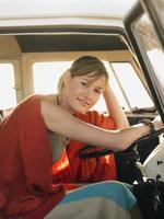 vrouw zit op de bestuurdersstoel van camper foto