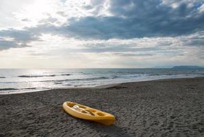 gele kano op een zandstrand in de buurt van de zee foto
