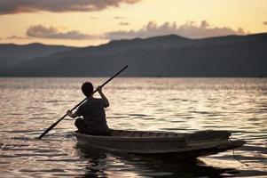 man peddelen een traditionele kano foto