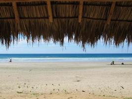 rustig strand met palmblad cabana. foto