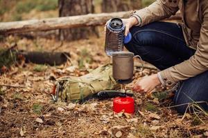 vrouw giet water uit een fles in een mok foto